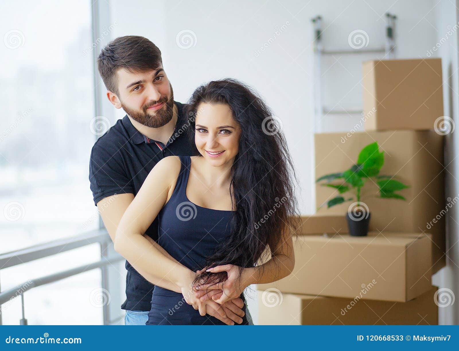 Pares novos felizes que movem-se na casa nova que desembala caixas