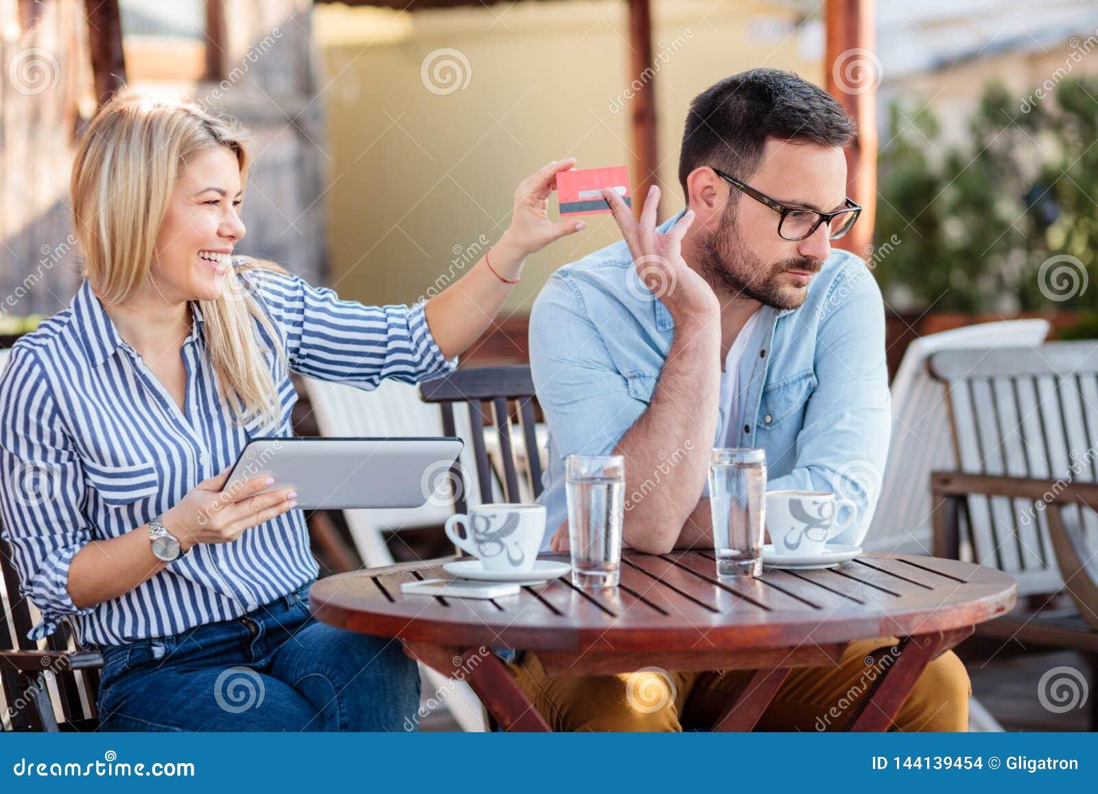 Pares novos felizes que sentam-se em um café e que compram em linha Mulher que toma o cartão de crédito de seu noivo
