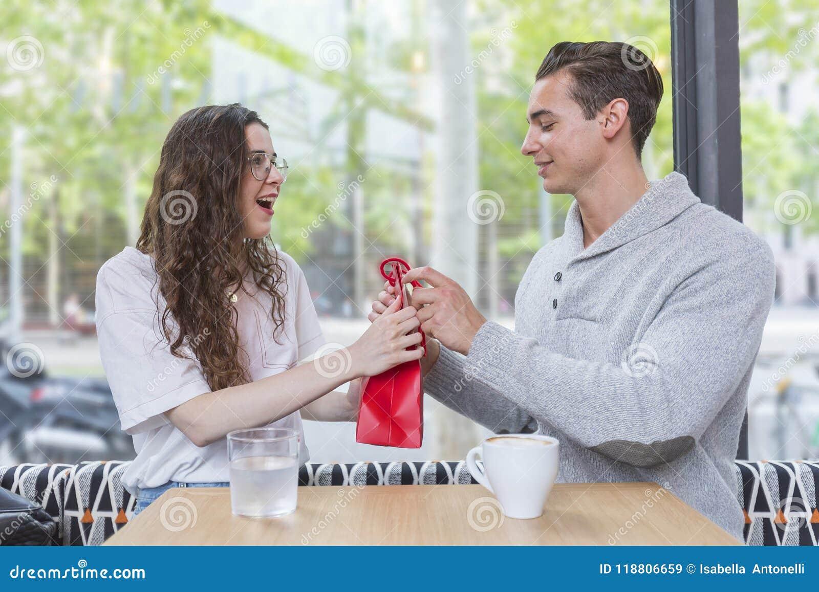 Pares novos felizes que sentam-se na tabela do café com um presente