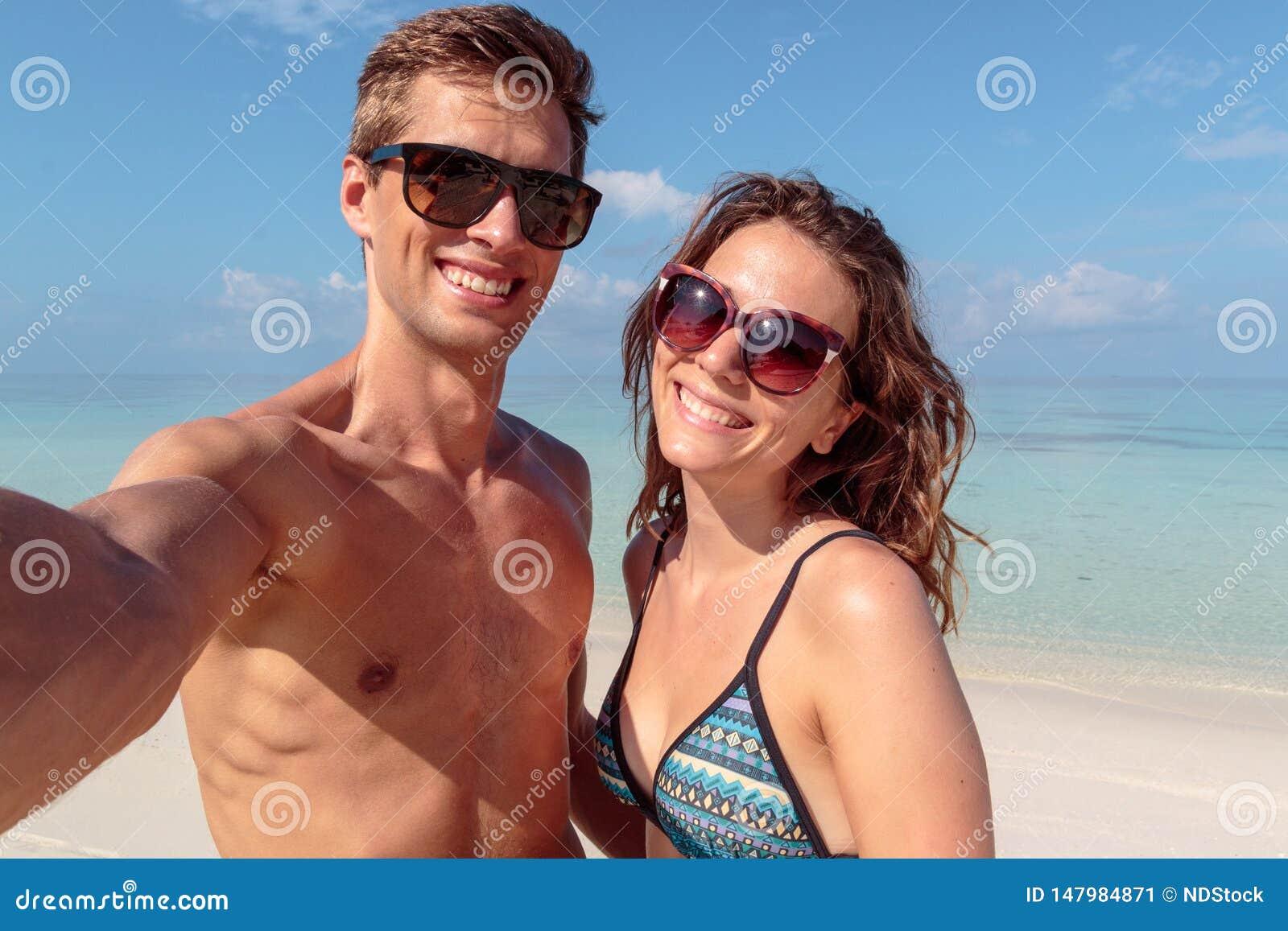 Pares novos felizes que tomam um selfie, água azul clara como o fundo hug