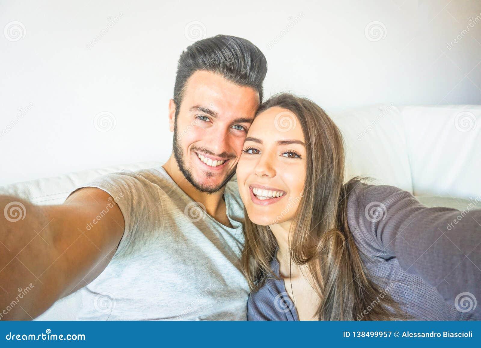 Pares novos felizes que tomam um selfie com a câmera esperta móvel do telefone na sala de visitas que abraça no sofá em casa