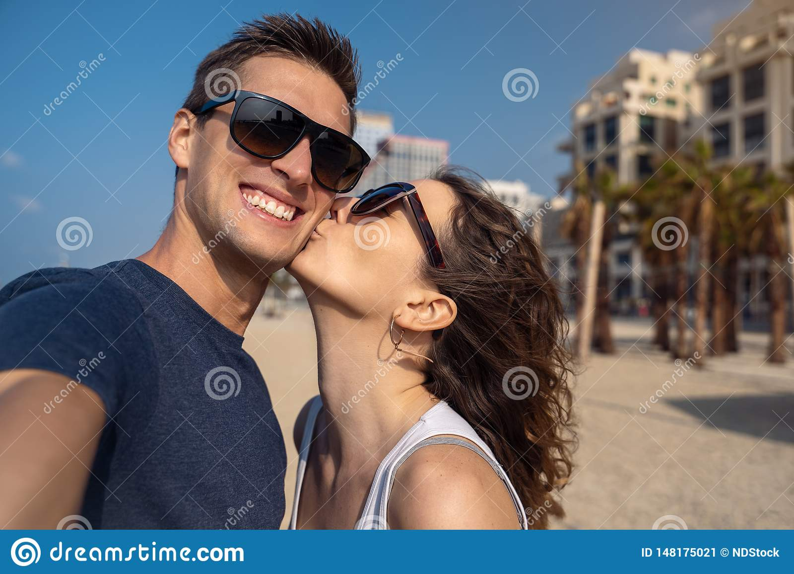 Pares novos felizes que tomam um selfie na praia em Tel Aviv