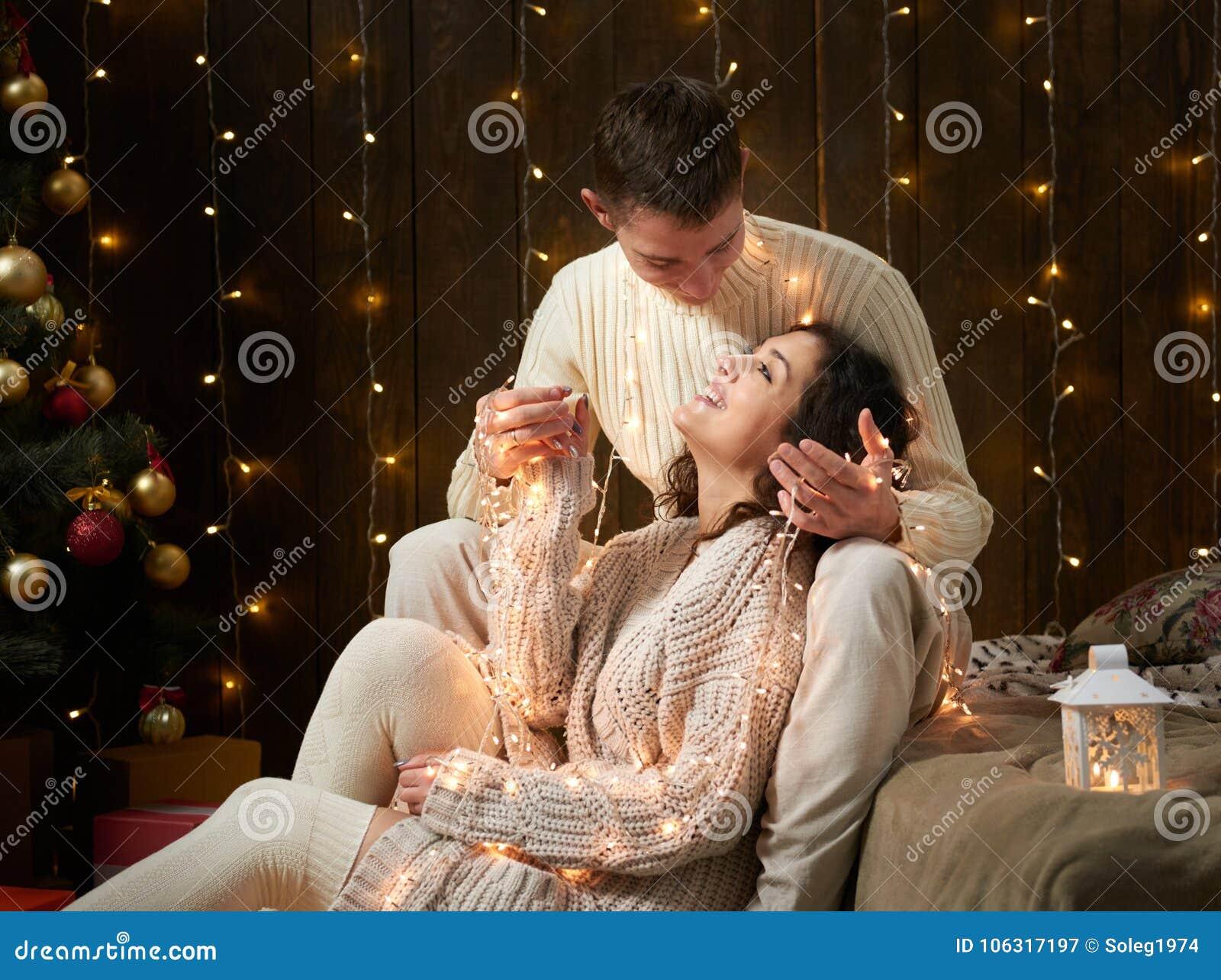 Pares novos junto nas luzes e na decoração de Natal, vestidas no branco, árvore de abeto no fundo de madeira escuro, noite românt