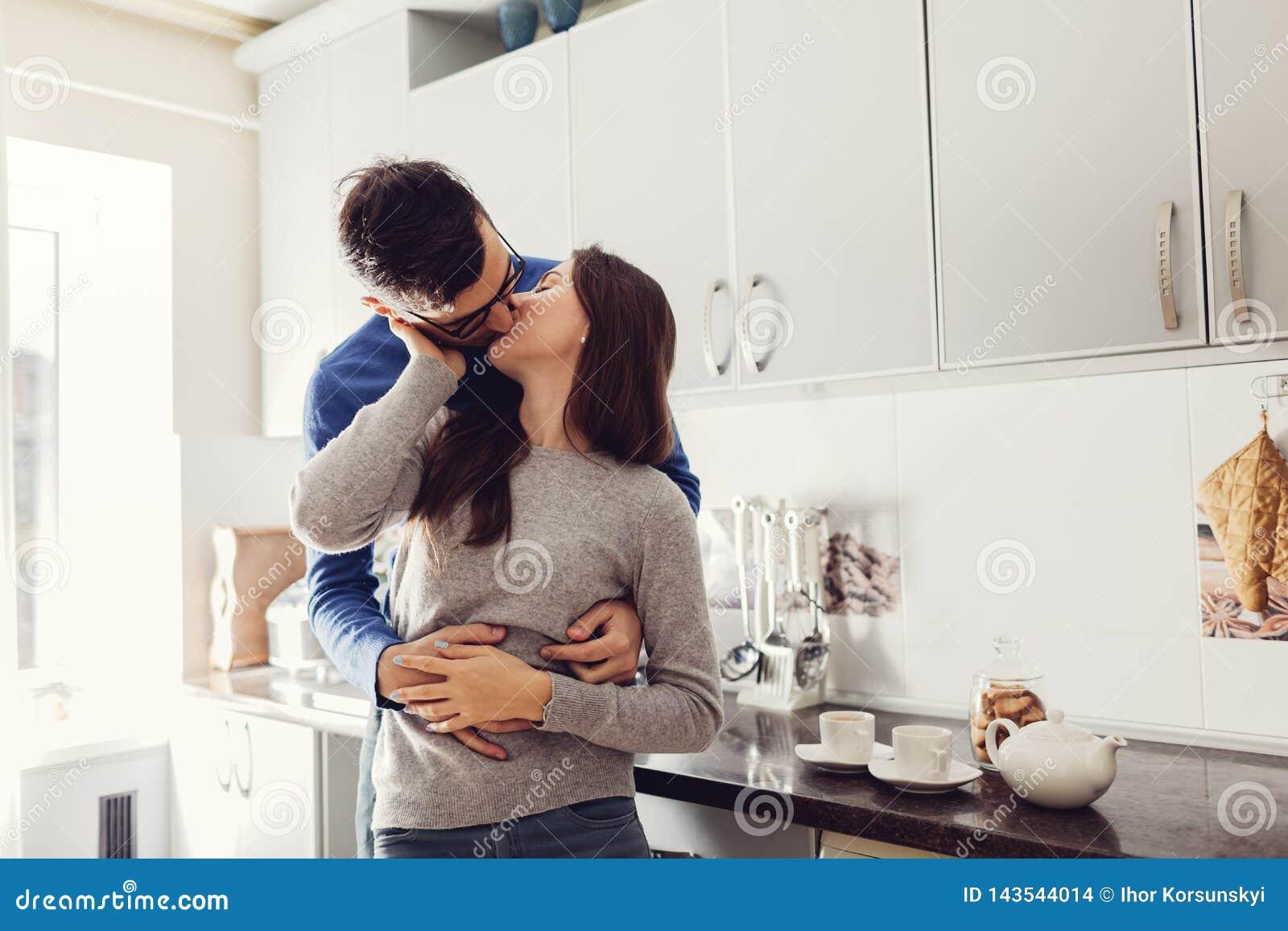 Pares novos na cozinha que abraça e que beija