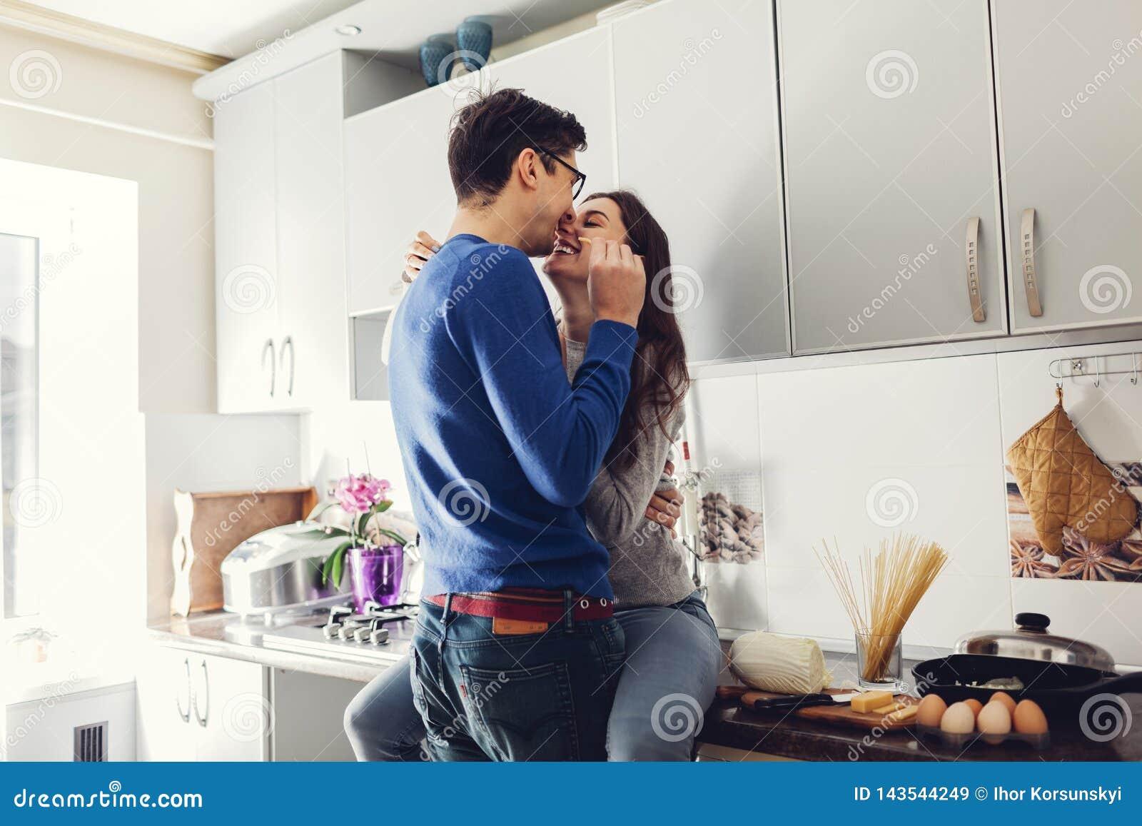 Pares novos na cozinha que abra?a e que come o queijo