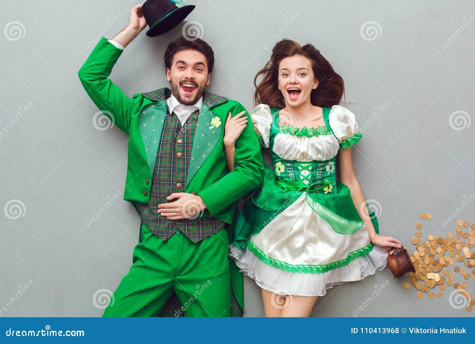 Pares novos na opinião superior do dia festivo do ` s de St Patrick dos trajes que olha a câmera surpreendida