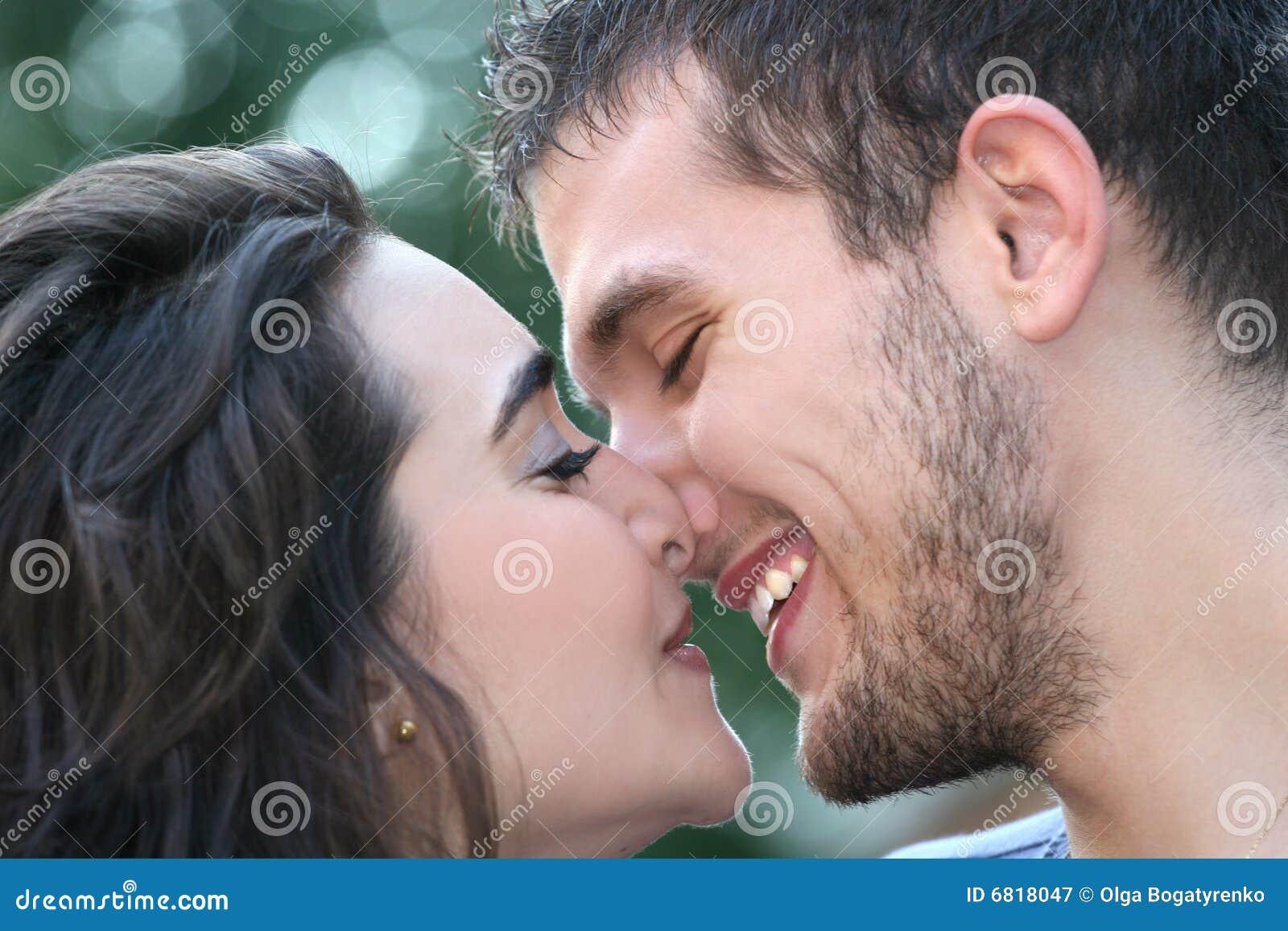 Pares novos no amor, beijando, ao ar livre