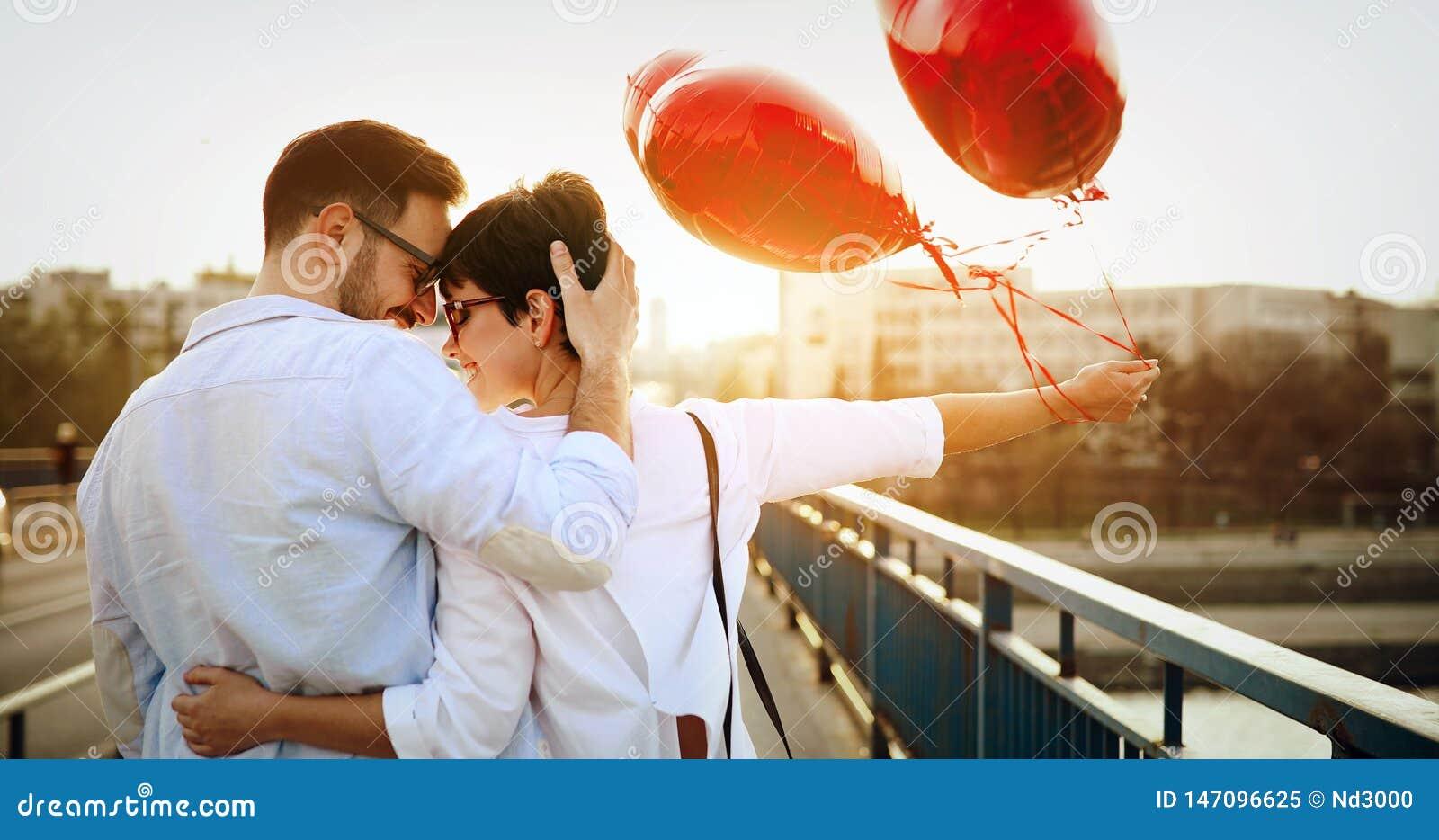 Pares novos no amor que data e que sorri exterior