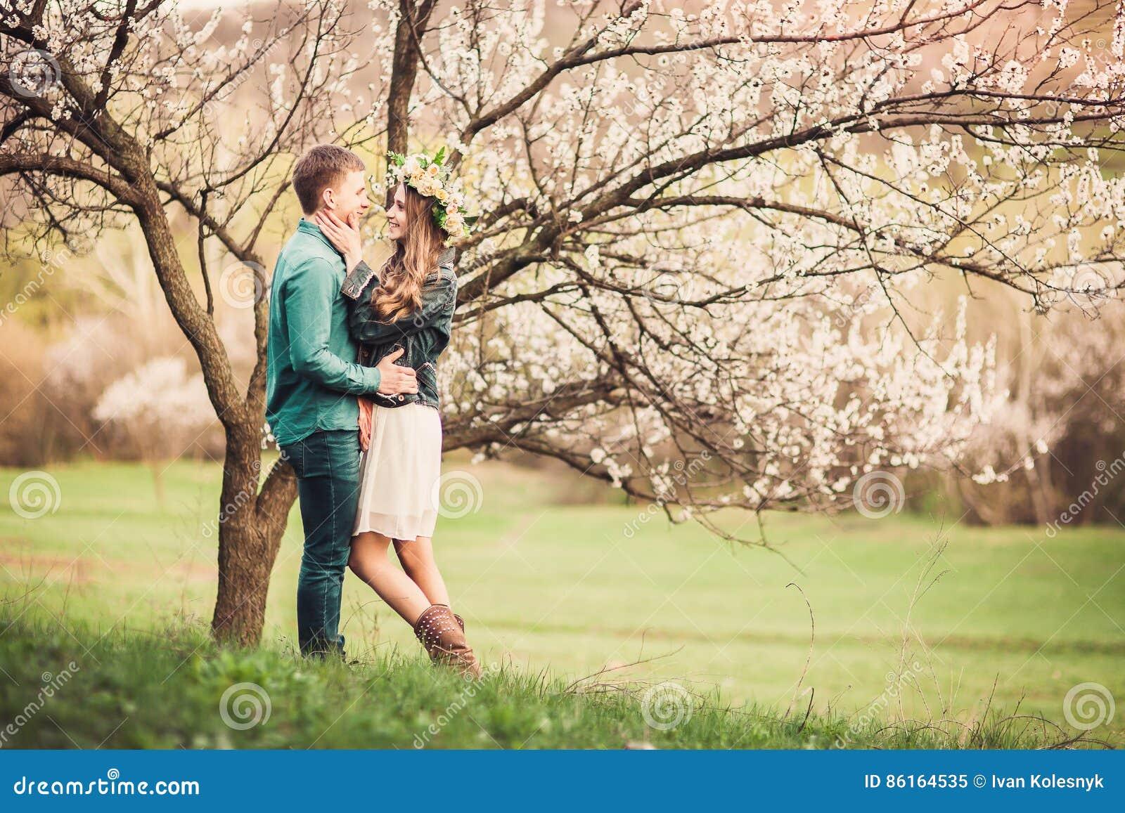 Pares novos no amor que tem uma data sob árvores cor-de-rosa da flor