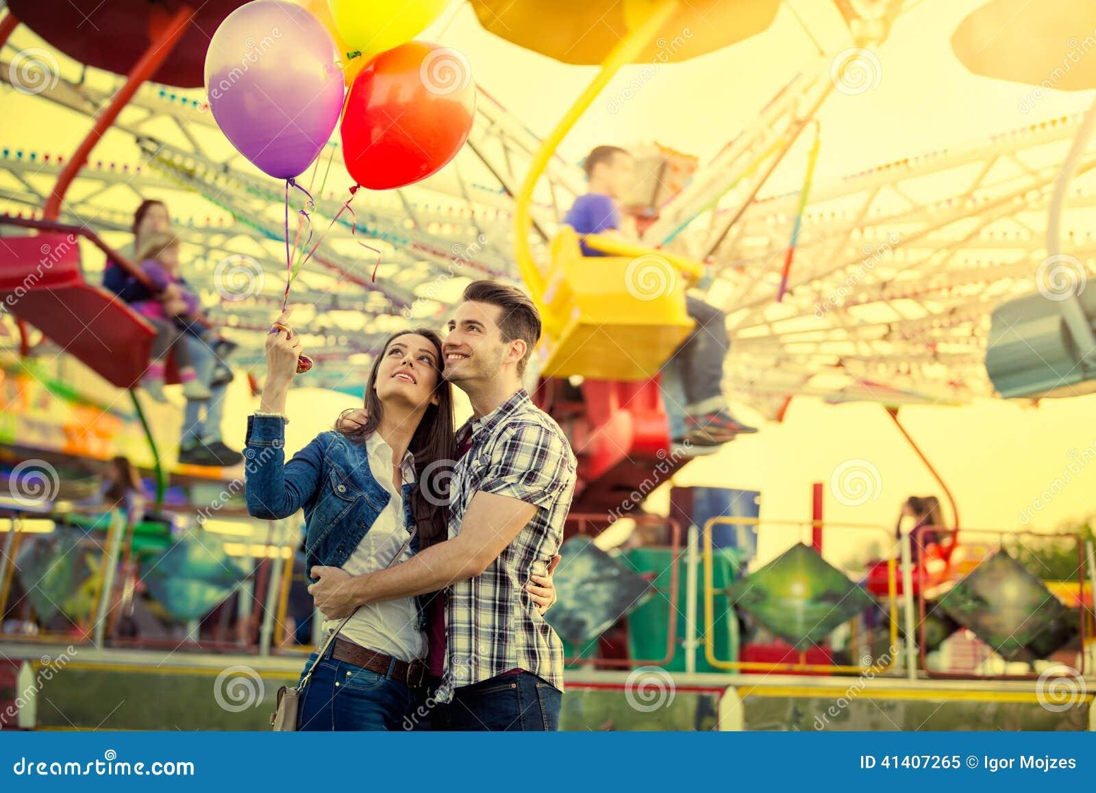 Pares novos que abraçam no parque de diversões
