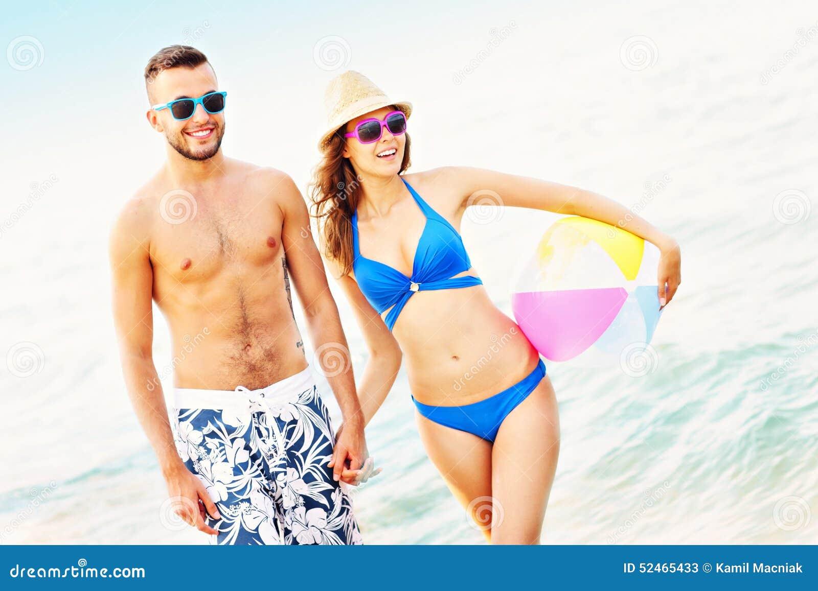 Pares novos que andam ao longo da praia