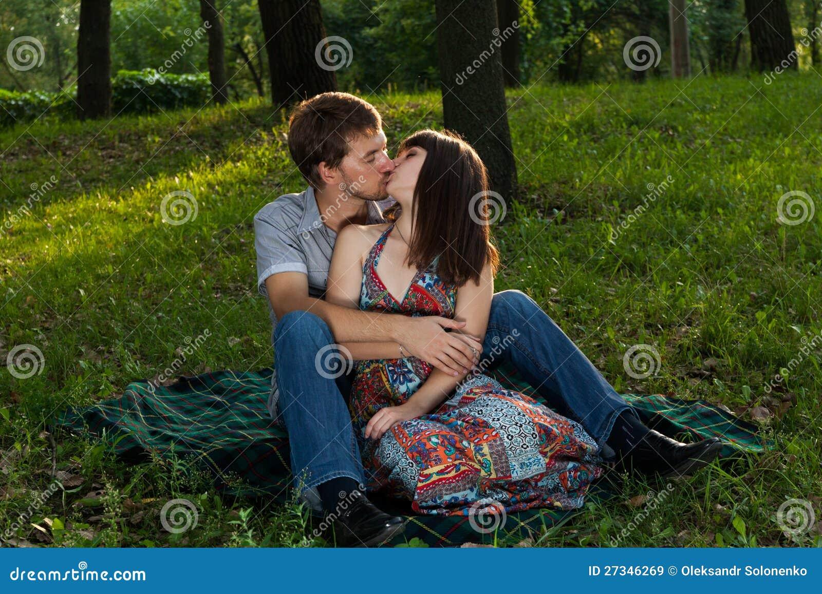 Pares novos que beijam em um piquenique romântico