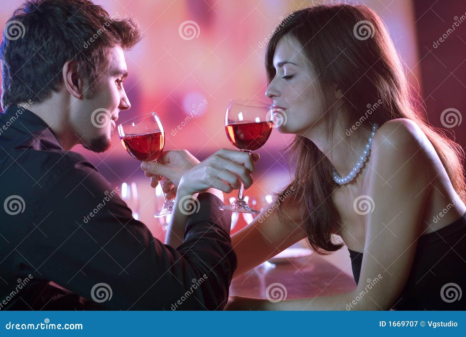 Pares novos que compartilham de um vidro do vinho vermelho no restaurante, celebrat