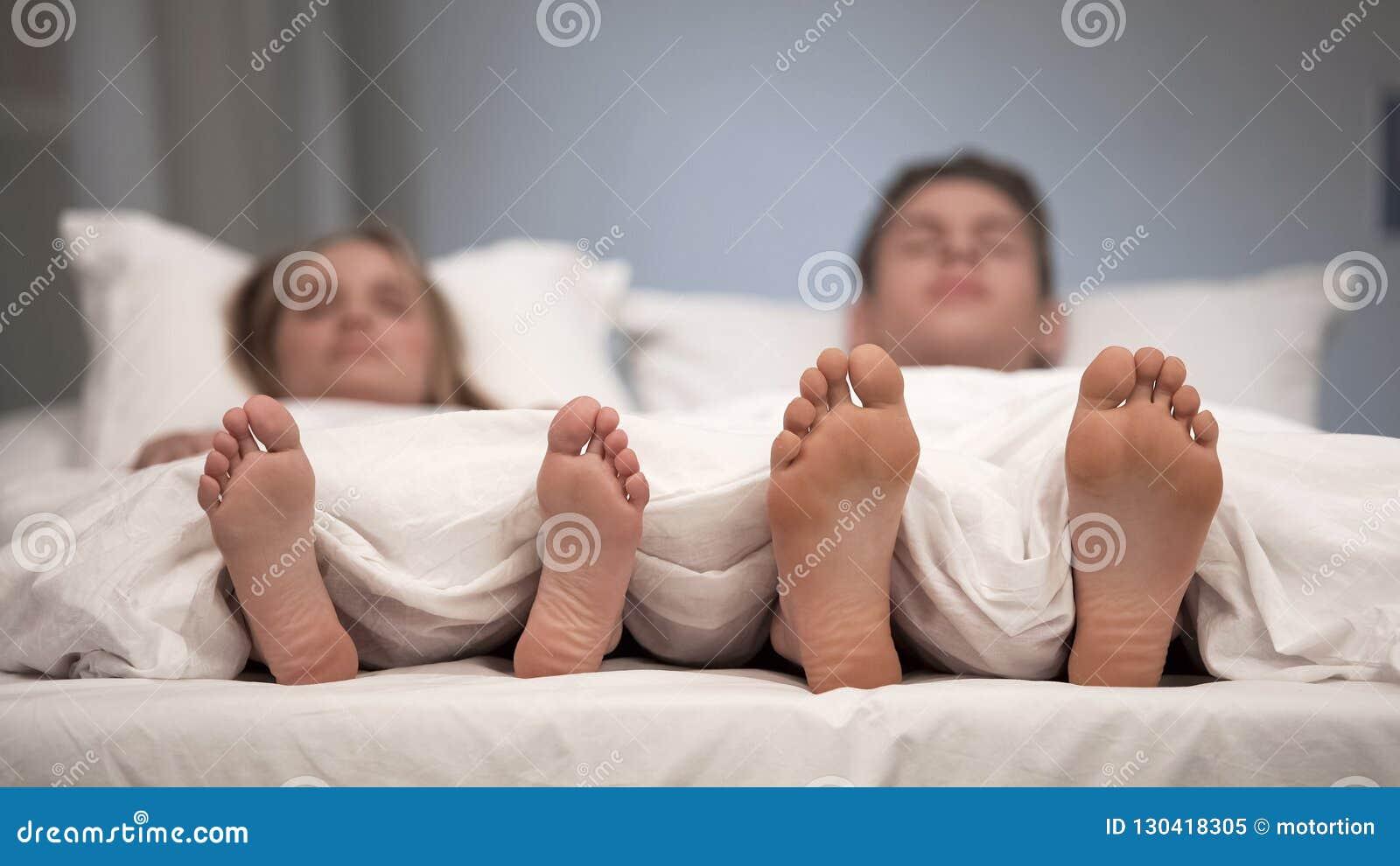 Pares novos que dormem na cama, ideia dos pés saudáveis, efeito antifungoso do pulverizador
