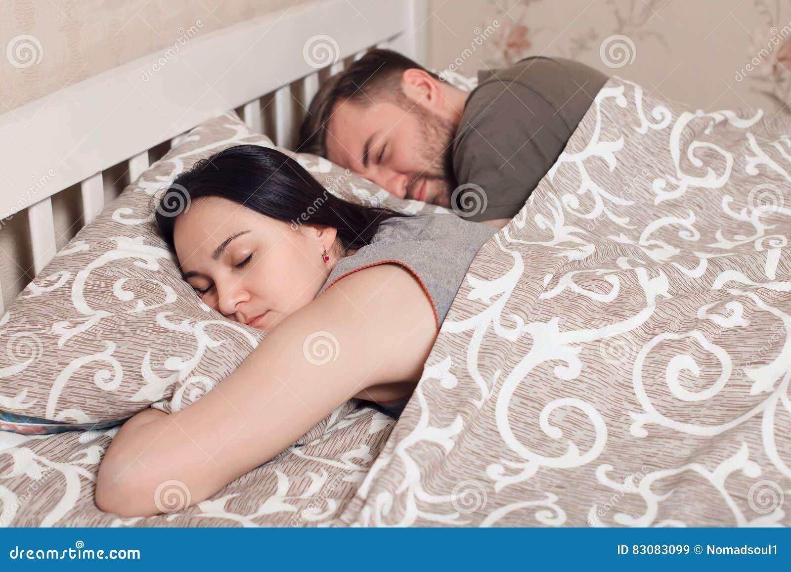 Pares novos que dormem na cama sob a cobertura