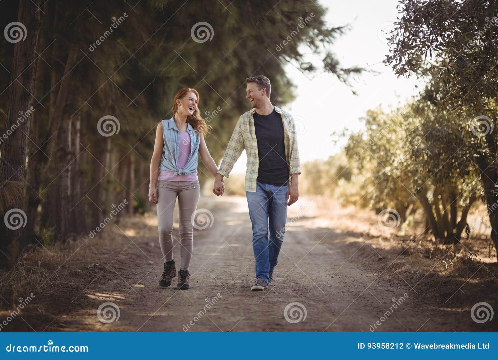 Pares novos que guardam as mãos ao andar na estrada de terra na exploração agrícola verde-oliva