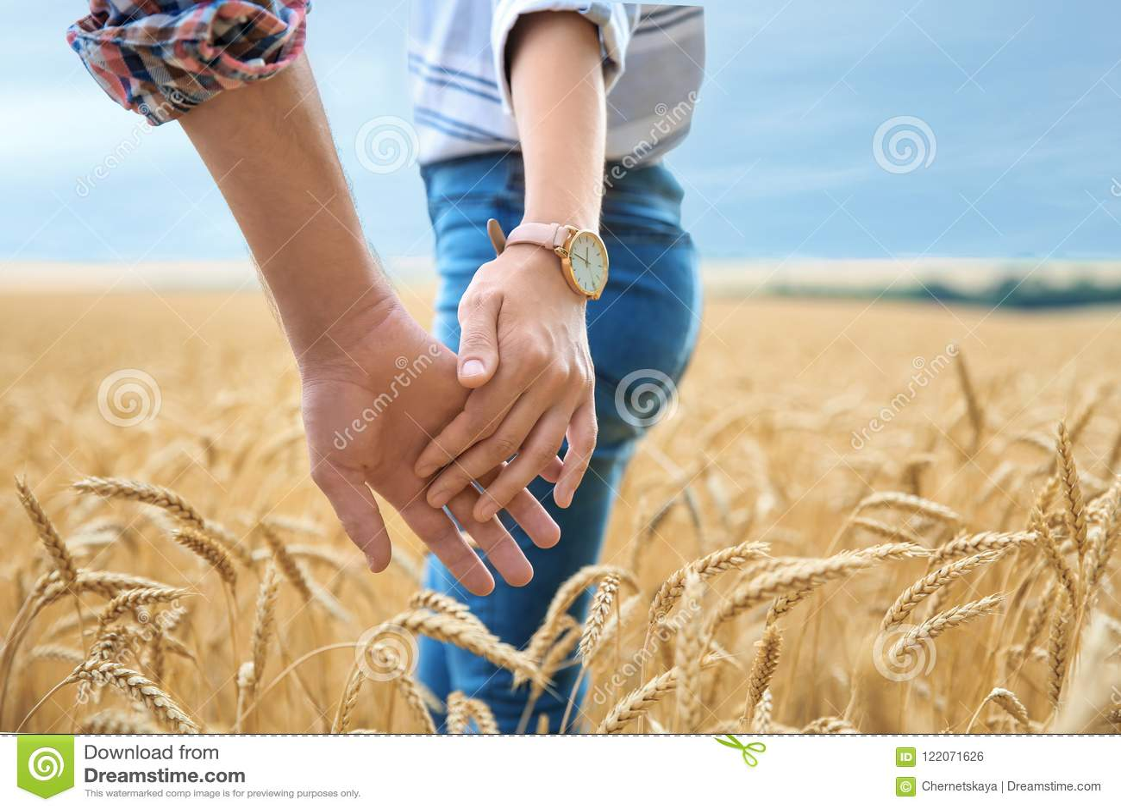 Pares novos que guardam as mãos no campo de grão