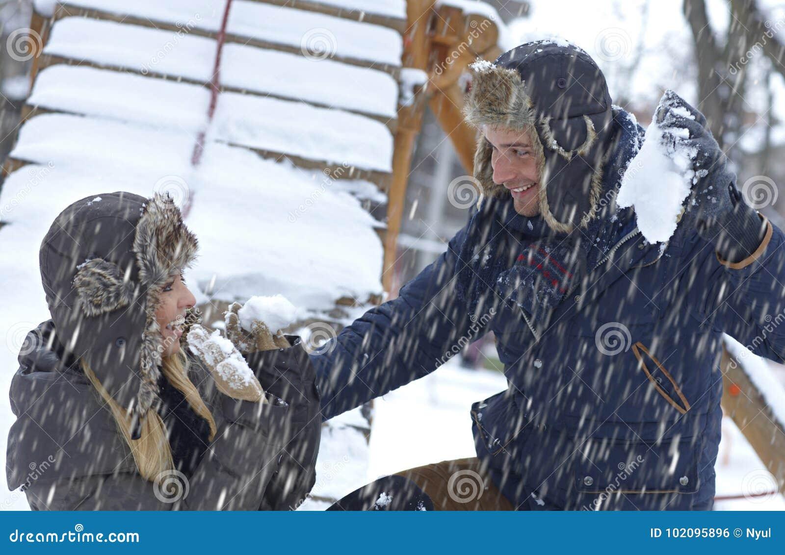 Pares novos que jogam na queda de neve