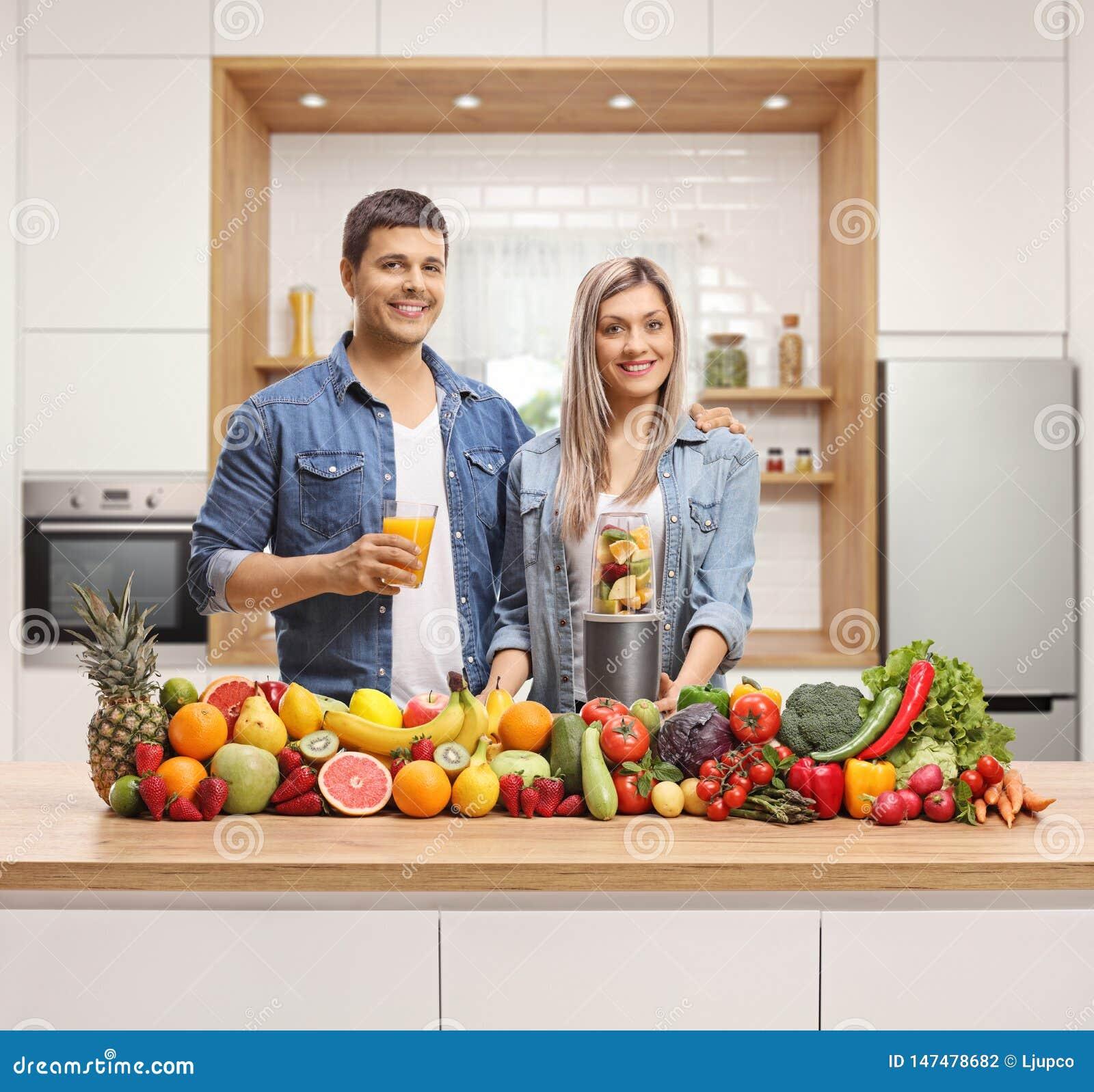 Pares novos que levantam atrás de um contador de cozinha com frutas e legumes
