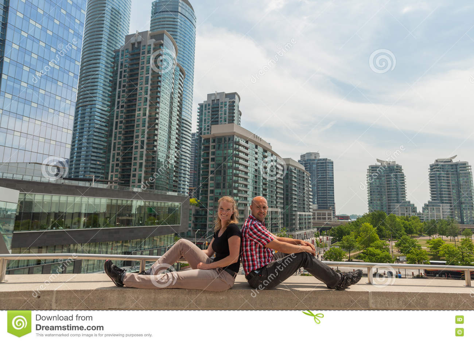 Pares novos que sentam-se em uma ponte em Toronto