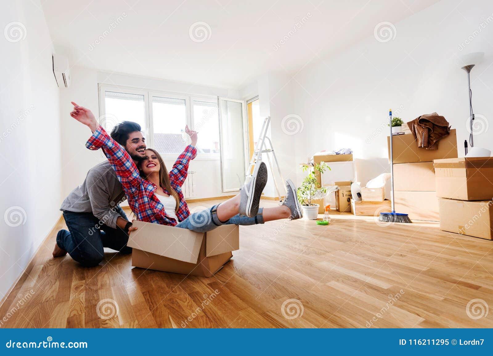 Pares novos que sentam-se no assoalho do apartamento vazio Mova-se dentro para a casa nova