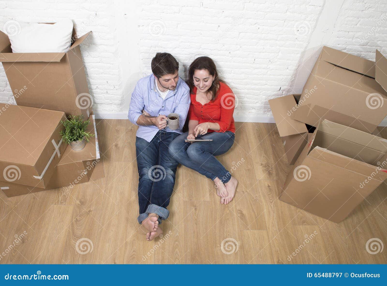 Pares novos que sentam-se no assoalho que move-se na casa nova usando a almofada digital da tabuleta