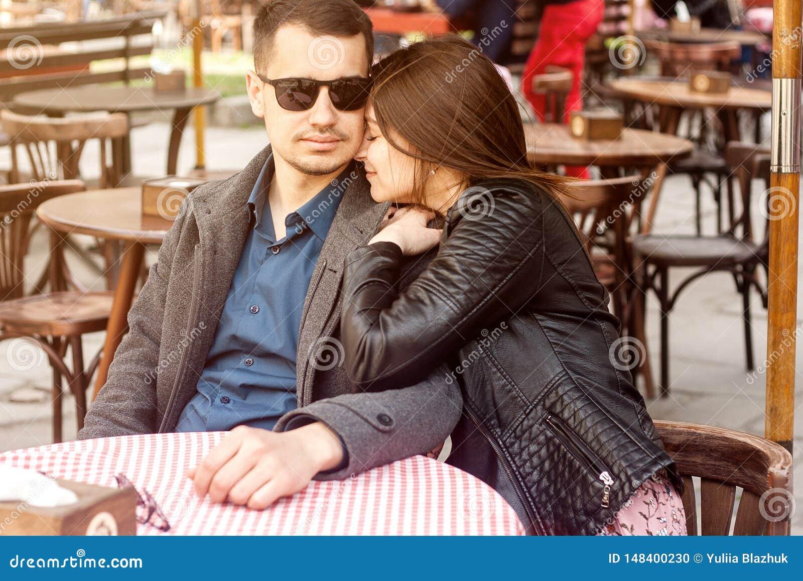 Pares novos que sentam-se no caf? da rua que tem a data rom?ntica