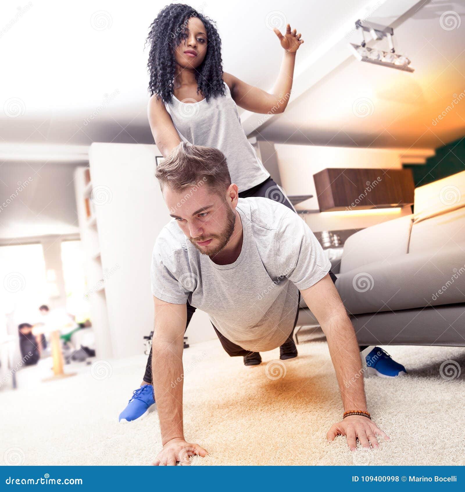 Pares novos que têm o divertimento que faz a ginástica em casa