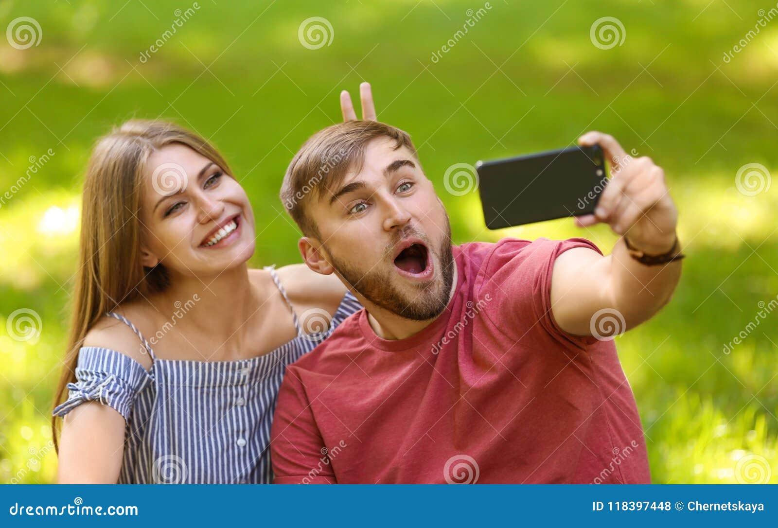 Pares novos que tomam o selfie na grama verde no parque