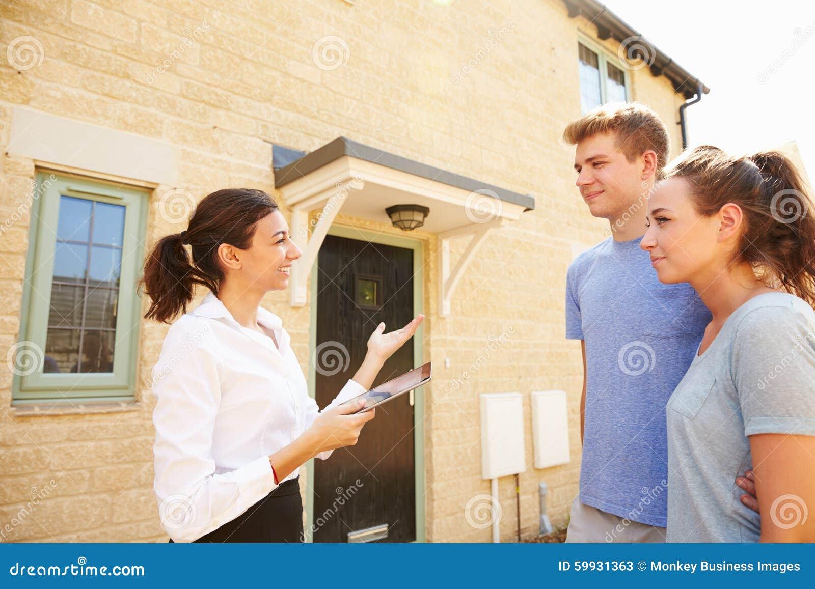 Pares novos que veem uma casa com o mediador imobiliário fêmea