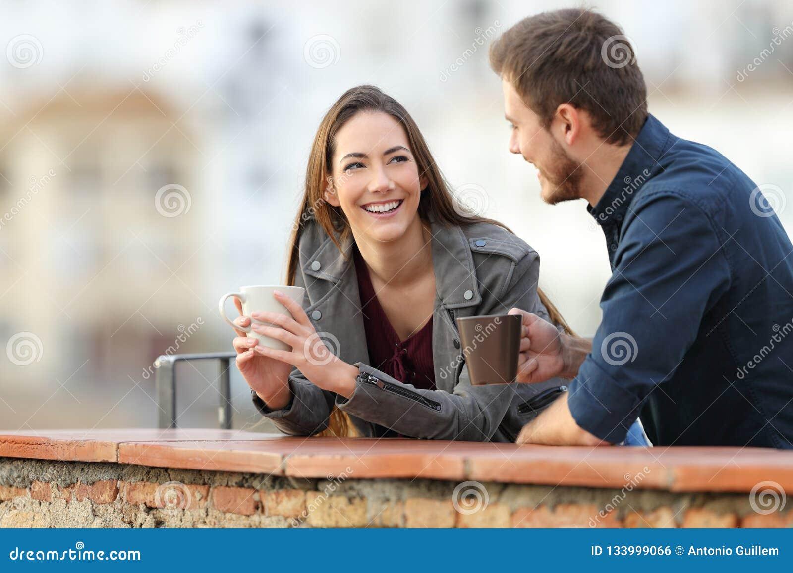 Pares ou amigos que falam em um café bebendo do terraço