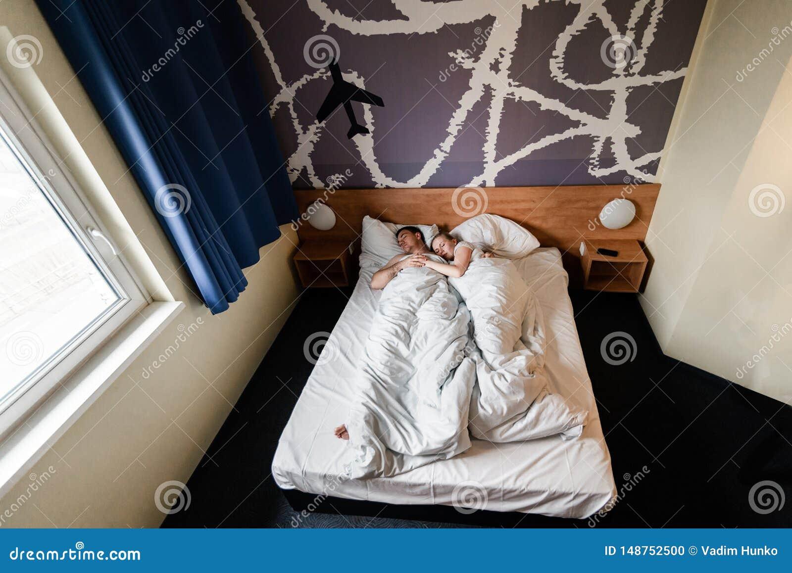 Pares ou fam?lia nova feliz bonita que acordam junto na cama