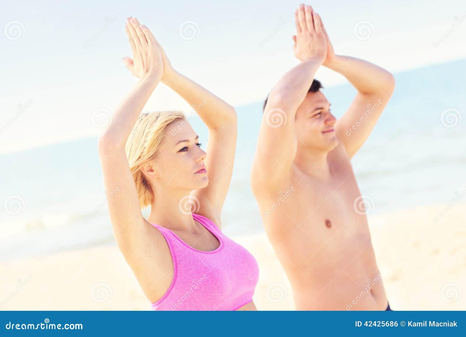 Pares pacíficos que meditan en la playa