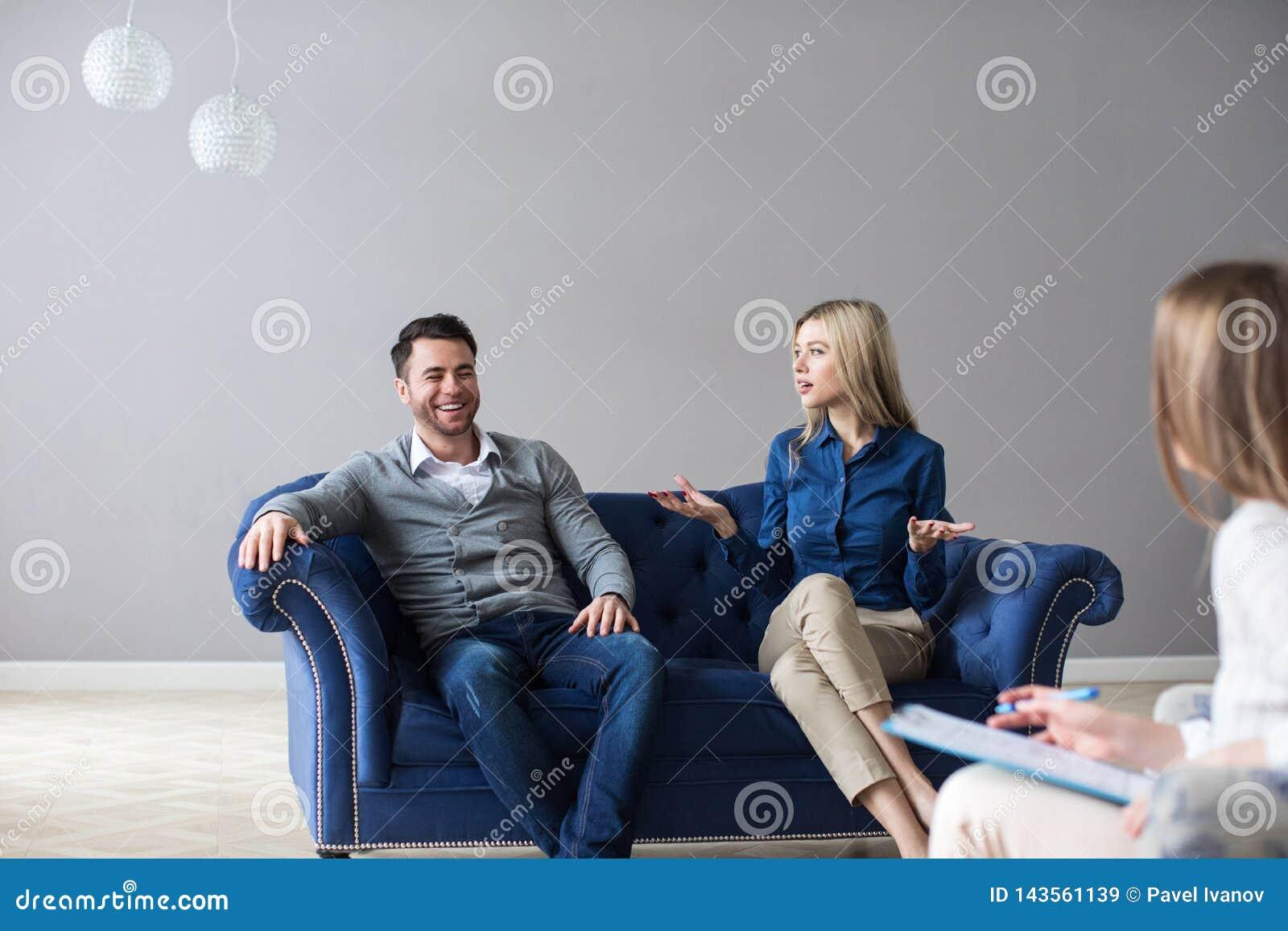 Pares preocupados que escutam o psicólogo durante uma terapia que senta-se em um sofá em casa