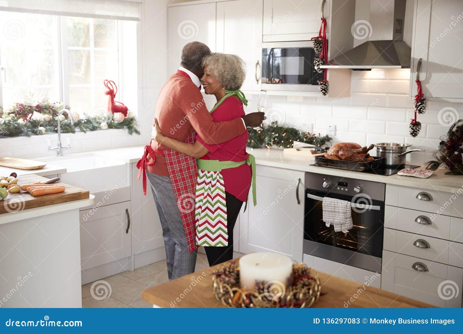 Pares pretos maduros felizes que guardam vidros do champanhe, rindo e abraçando na cozinha ao preparar a refeição no morni do Nat