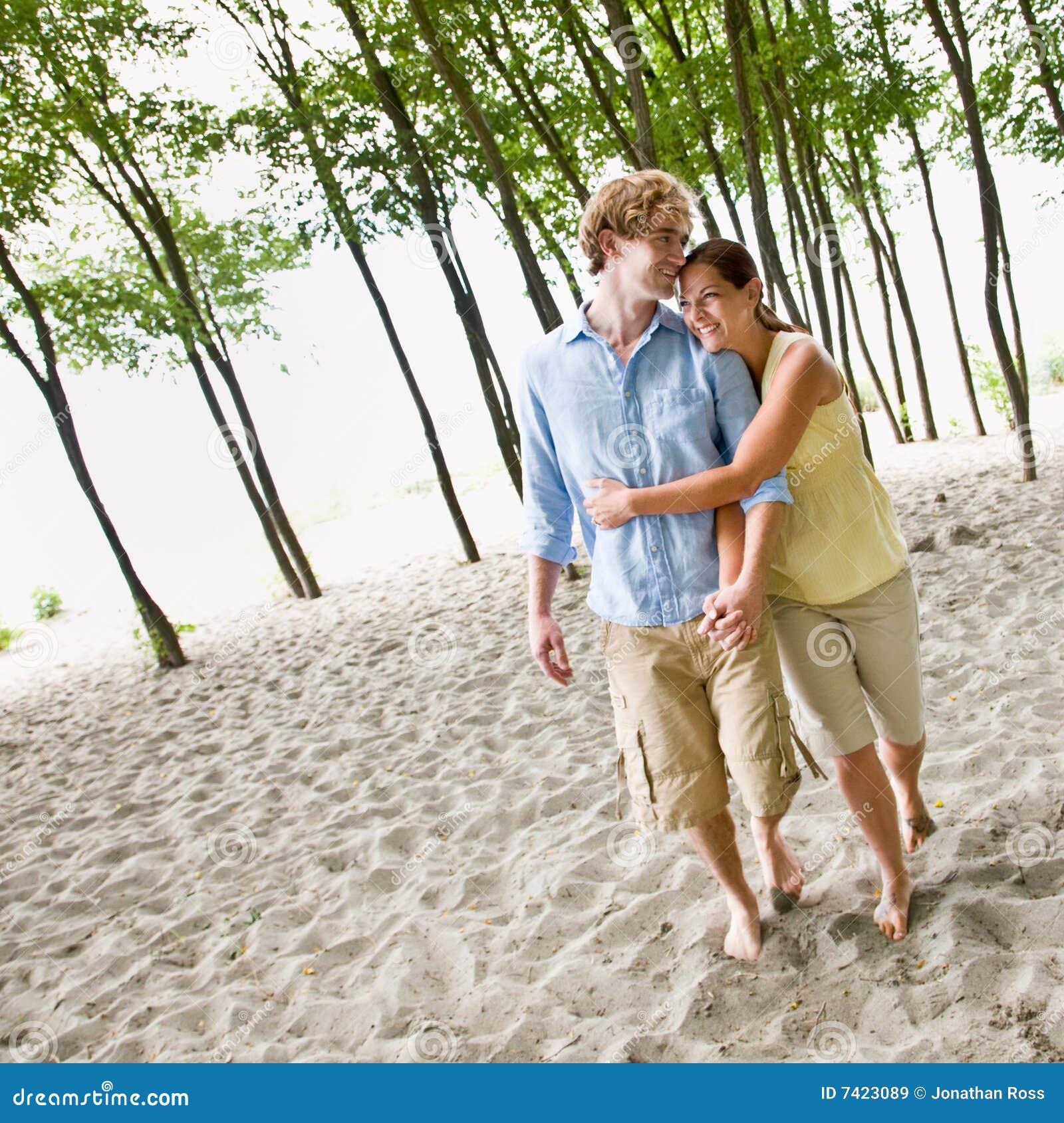 Pares que abrazan en la playa
