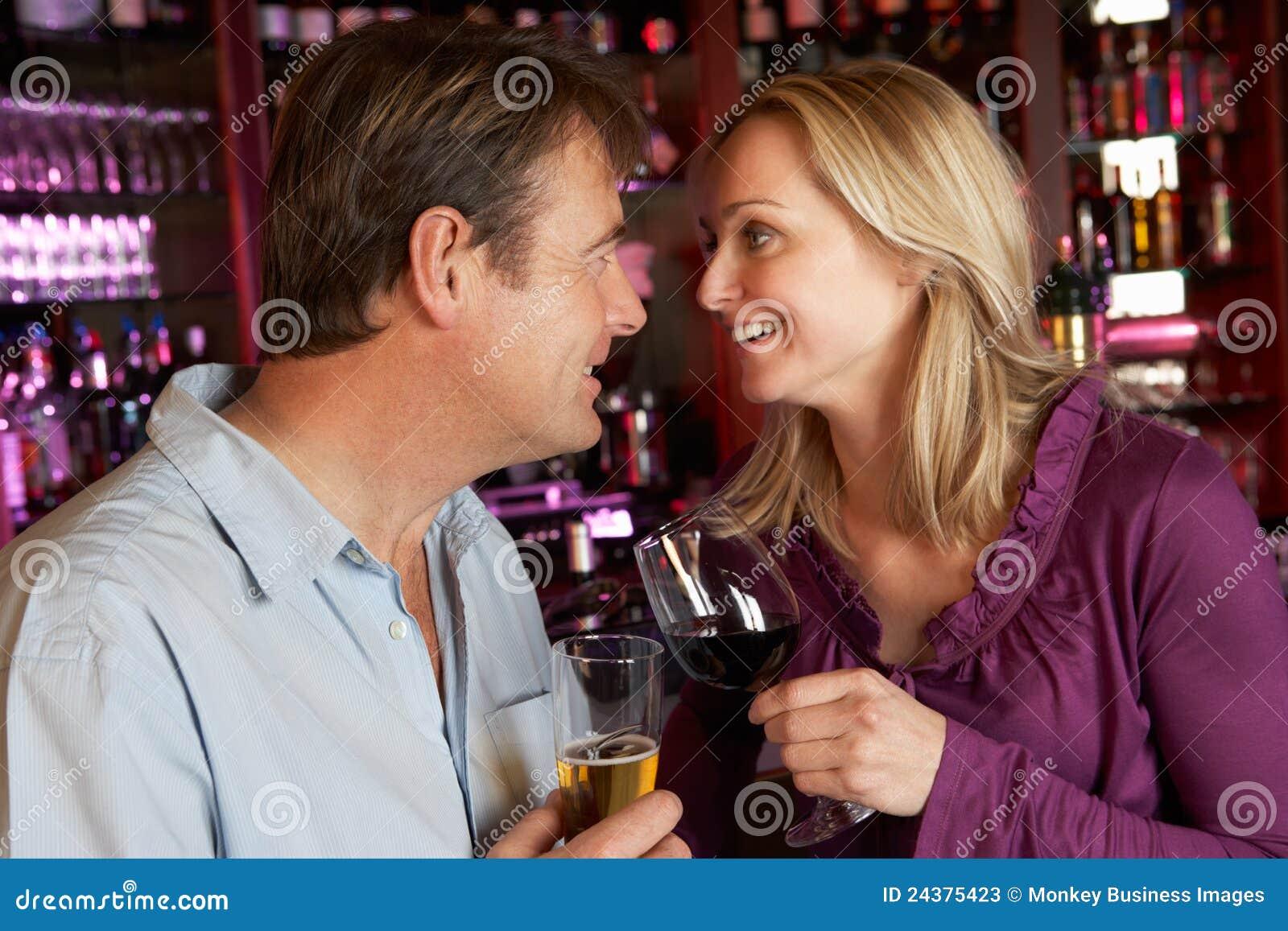 Pares que apreciam a bebida junto na barra