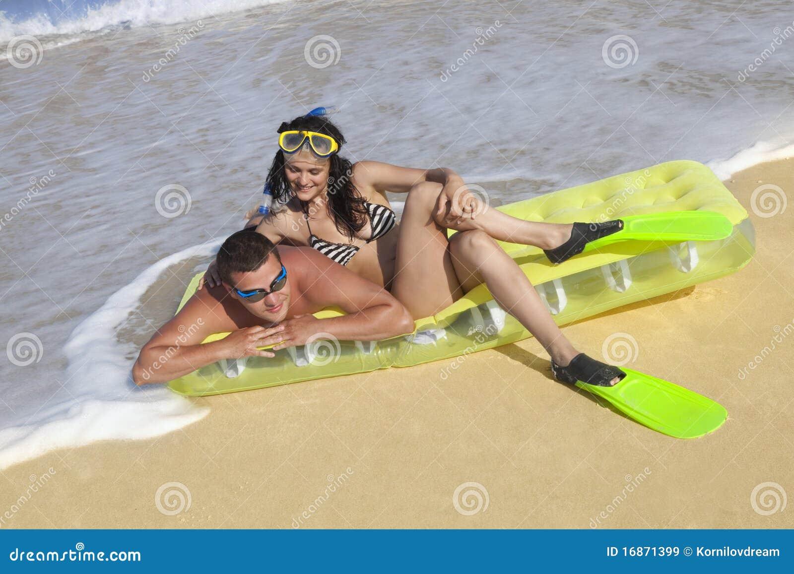 Pares que apreciam em um colchão inflável da praia