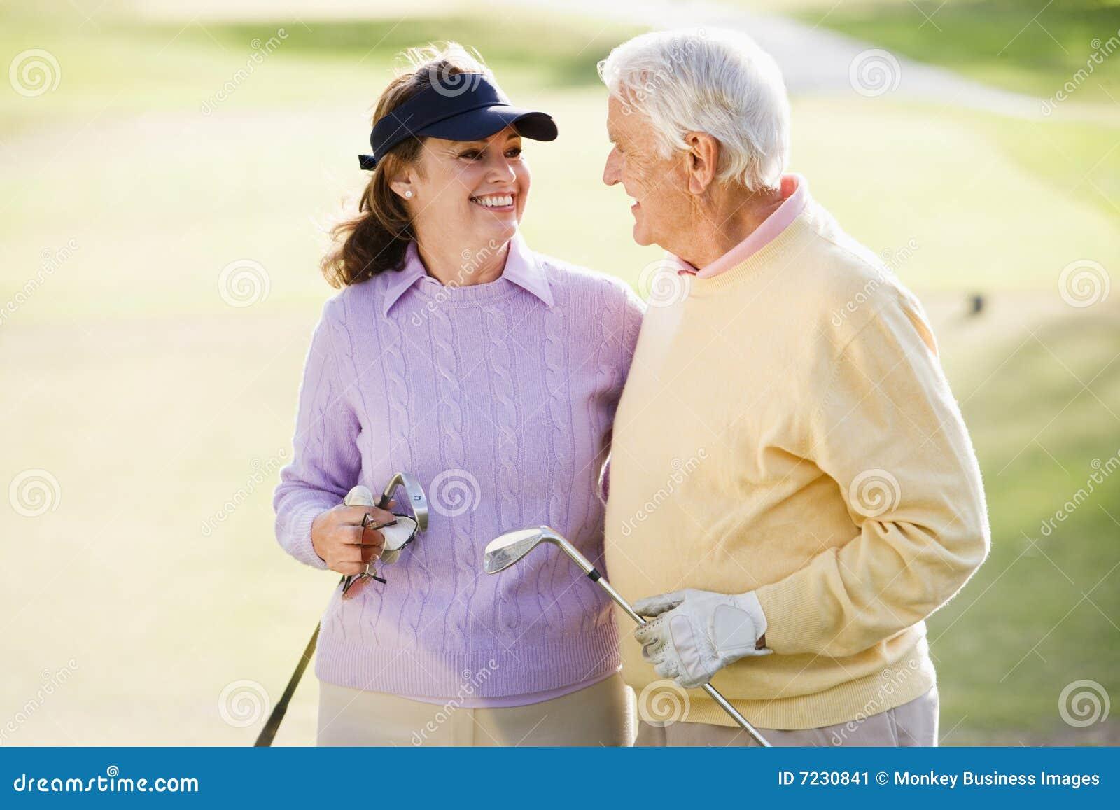 Pares que apreciam um jogo do golfe
