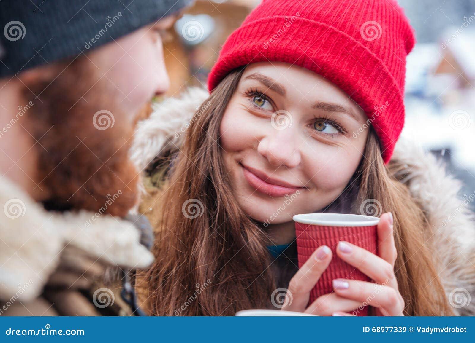 Pares que beben el café caliente al aire libre en invierno