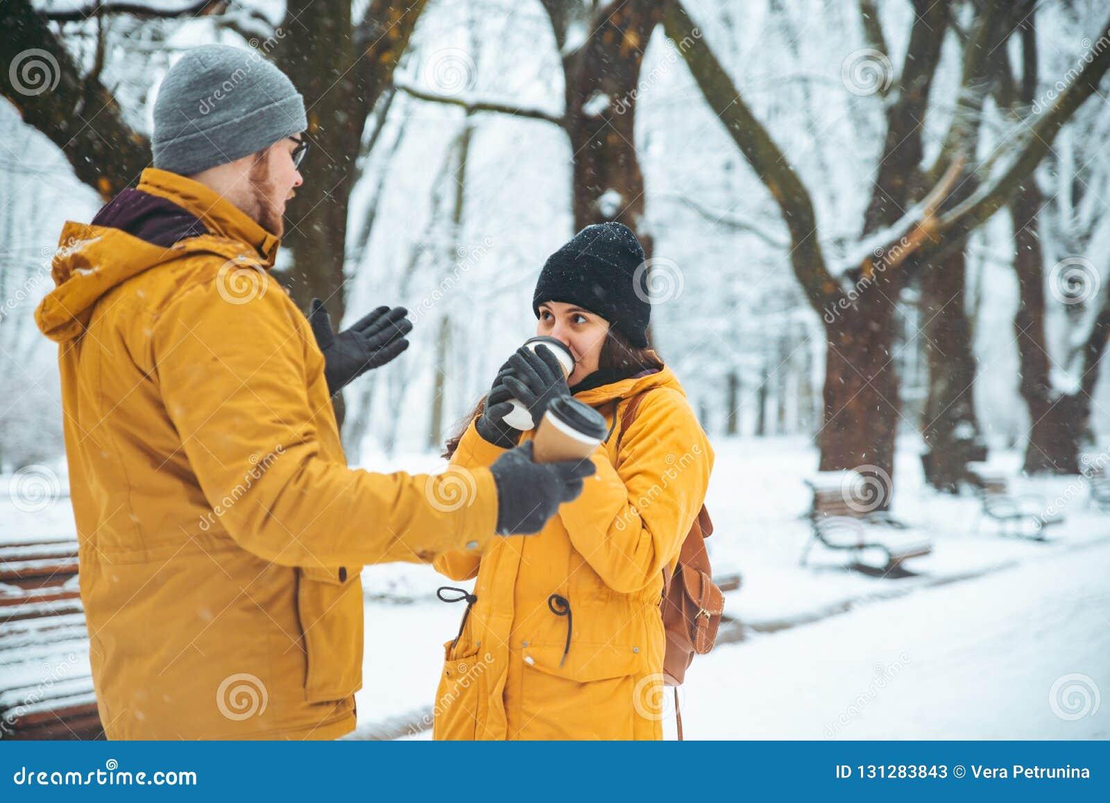 Pares que caminan por la socialización que habla nevada del parque de la ciudad fecha romántica en invierno
