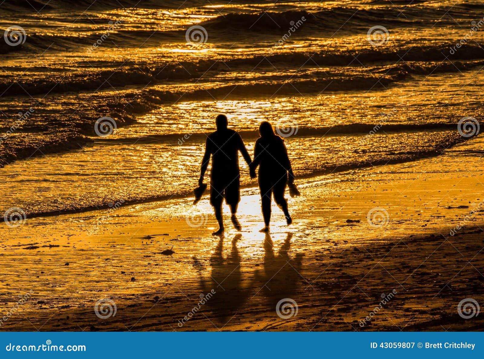 Pares que caminan sosteniendo la playa de las manos