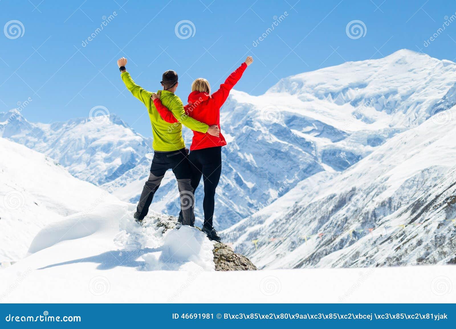 Pares que caminham montanhas do inverno do sucesso