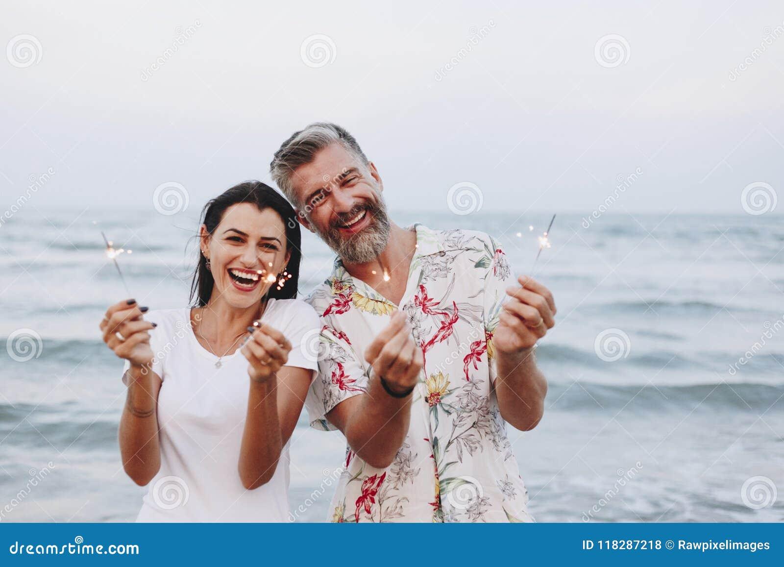 Pares que celebran con las chispas en la playa