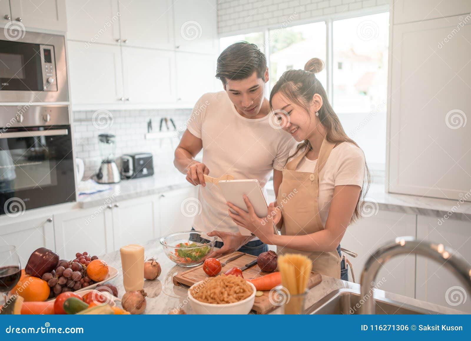 Pares que cocinan junto en la cocina en casa mirada de la PC de la tableta