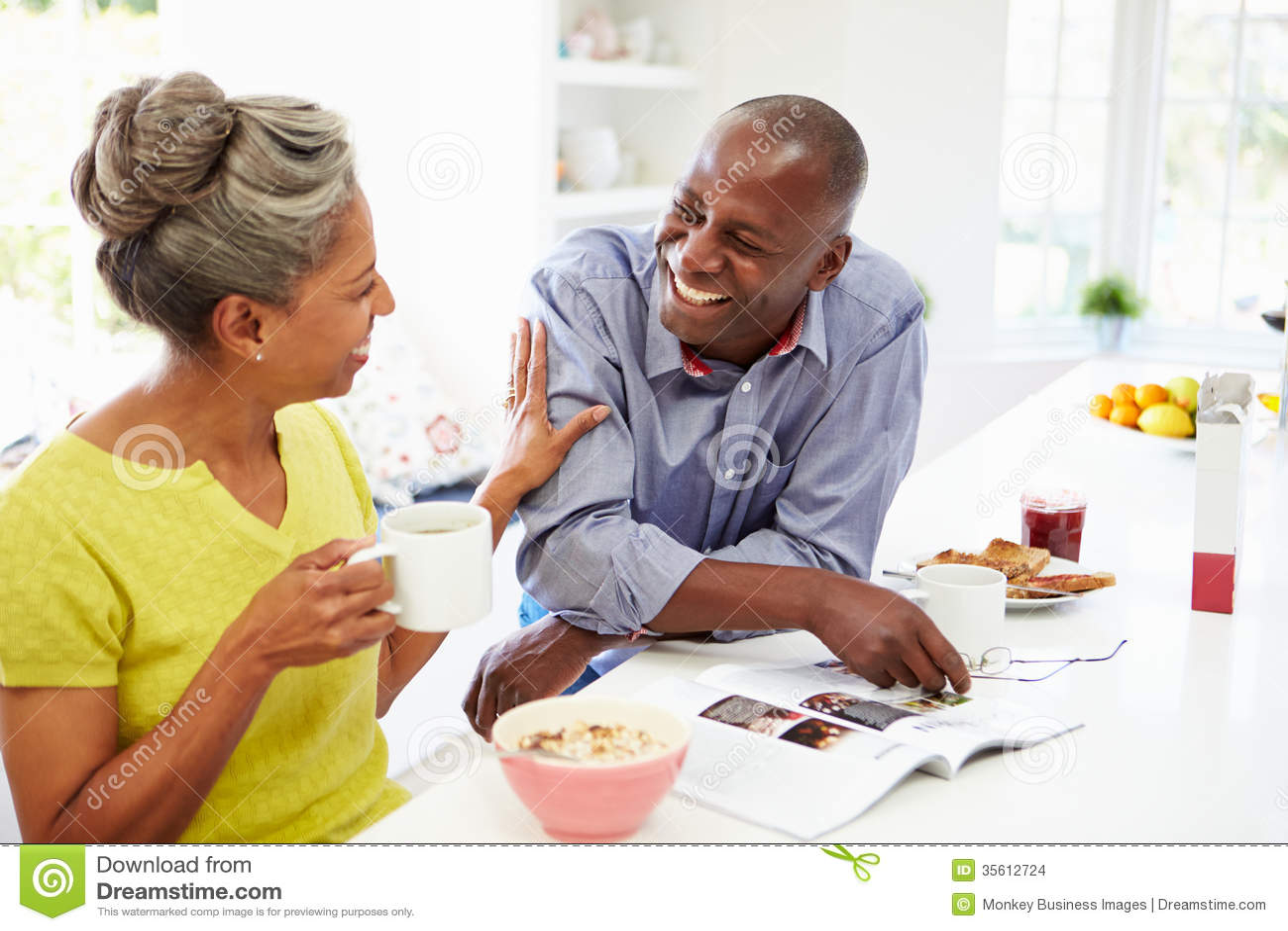 Pares que comem o café da manhã e que leem o compartimento na cozinha