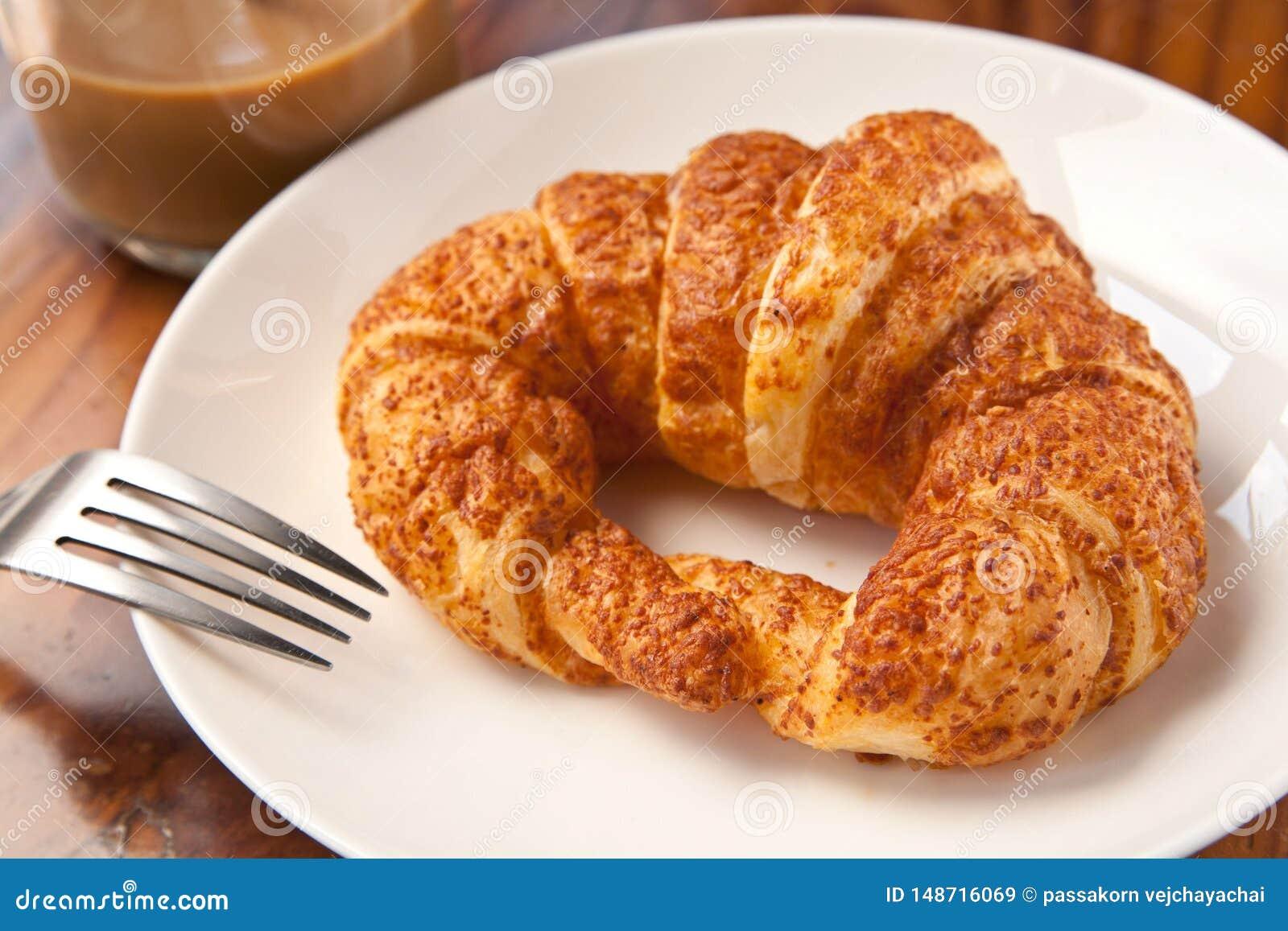 Pares que comem o croissant do caf? da manh? com caf?