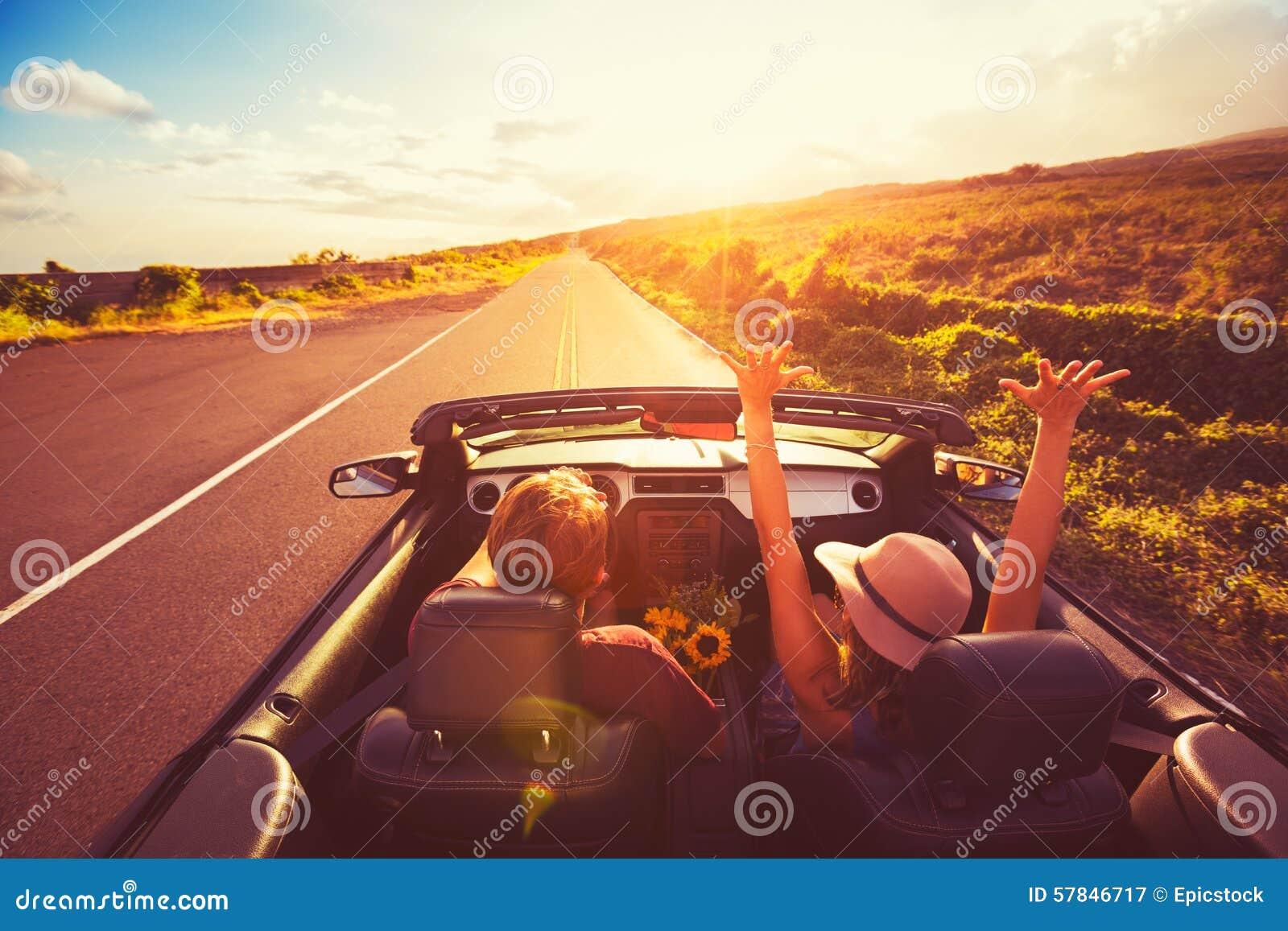 Pares que conduzem o convertible no por do sol