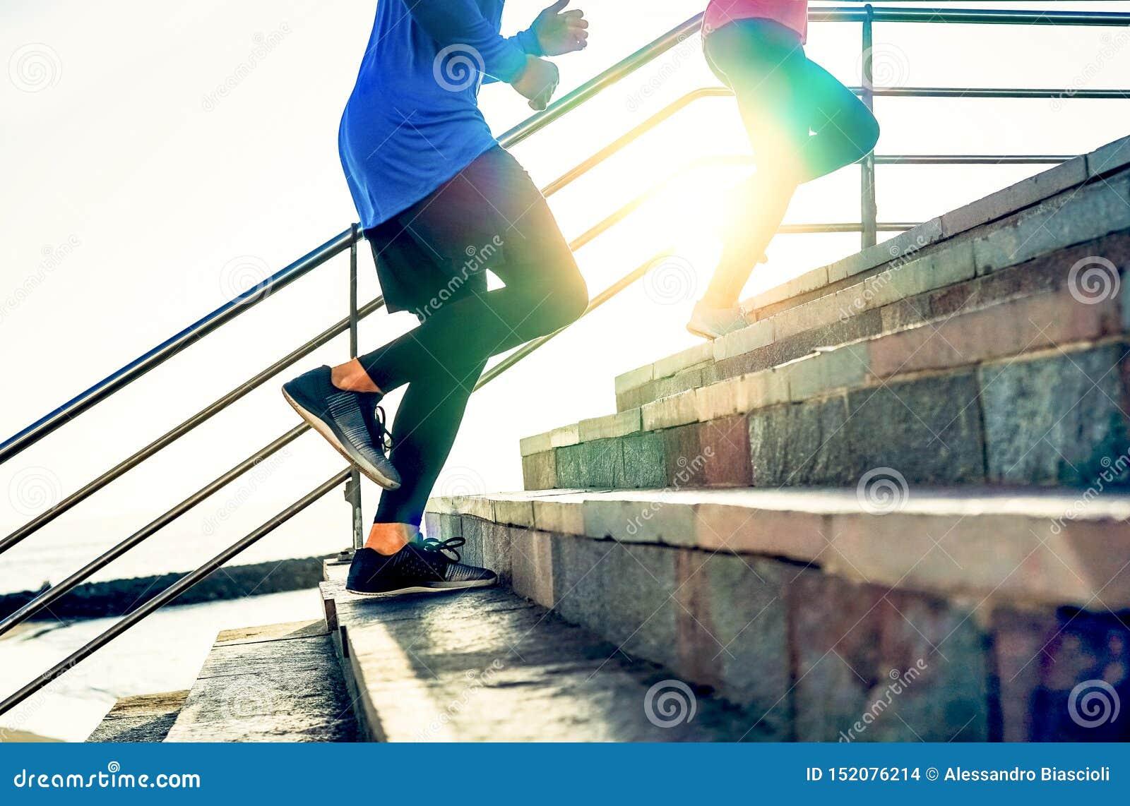 Pares que correm em escadas no por do sol - amigos que fazem uma sessão do exercício que exercita para obter na escadaria exterio