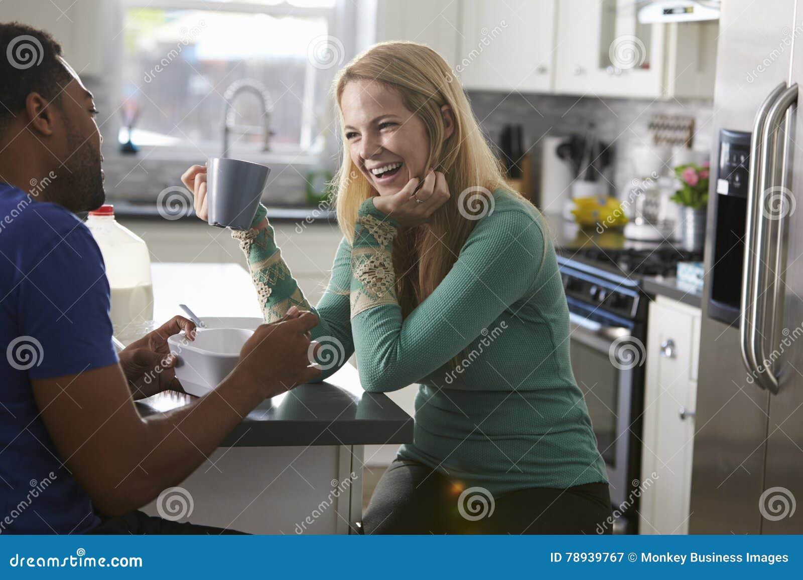 Pares que falam na cozinha, riso da raça misturada da mulher